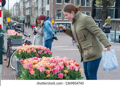 Amsterdam, The Netherlands - April 13, 2019: Amsterdam druing tulip festival in spring with people enjoying tulips on the Skinny Bridge (Magere Brug)