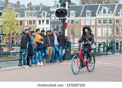 Amsterdam, The Netherlands - April 13, 2019: Happy tourists, ready for the picture, and passing cycling girl on the Skinny Bridge (Magere Brug).