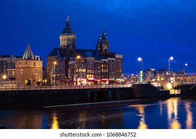 AMSTERDAM, NETHERLANDS - APRIL 14, 2018: The Saint Nicholas church next to the Schreierstoren in the historical part of Amsterdam with a blue sky in the blue hour after sunset
