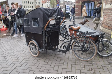 AMSTERDAM, NETHERLANDS - APRIL 15, 2016: Bike with baby cart on the street of Amsterdam.