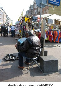 AMSTERDAM, NETHERLANDS - APRIL 15, 2017: People play musical instruments on a street in an outdoor flea market.
