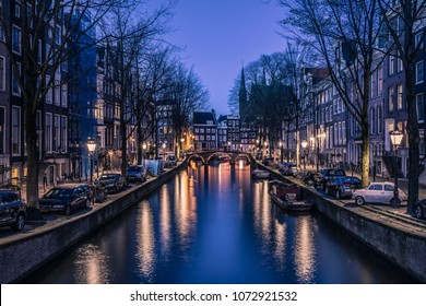 AMSTERDAM, NETHERLANDS - APRIL 15, 2018: The canal houses of Amsterdam along the water during the evening blue hour with orange lights and a bright blue sky