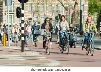 Amsterdam, The Netherlands - April 18, 2019: traffic, cyclists, scooter and pedestrians on a crossroad in Amsterdam in spring.