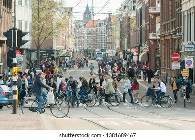 Amsterdam, The Netherlands - April 18, 2019: Traffic on a crossroad (Stadhouderskade) in Amsterdam. Many bicycles.