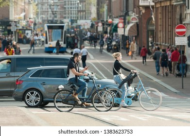 "Amsterdam, The Netherlands - April 18, 2019: cars and bicycles on a crossroad (Stadhouderskade), a cyclist using a smartphone. In the background street ""Ferdinand Bolstraat"", people and tram."