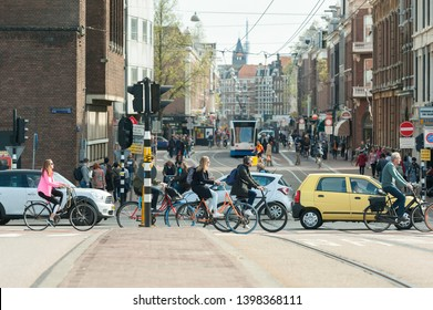 Amsterdam, The Netherlands - April 18, 2019: Traffic (bicycles, cars, tram pedestrians) in Amsterdam, crossroad busy streets Stadhouderskade/Ferdinand Bolstraat.