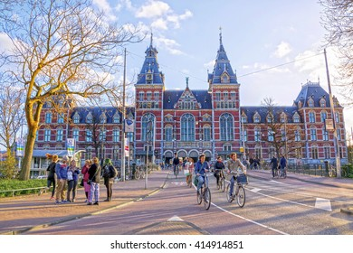 AMSTERDAM, Netherlands - APRIL 19, 2016: People on bicycles passing by Rijksmuseum (National state museum). Bicycle - the main means of transportation in Amsterdam