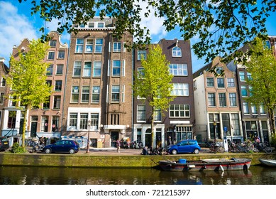 Amsterdam, Netherlands - April 19, 2017: Colorful houses and cars along the canal embankment in Amsterdam, Netherlands