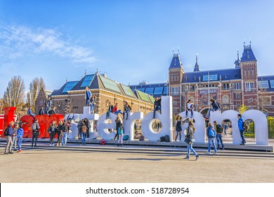 AMSTERDAM, Netherlands - APRIL 19,2016: Students and tourists are happy take photos on huge letters I Amsterdam - symbol of city, located on Museumplein in front of Rijksmuseum (National state museum)