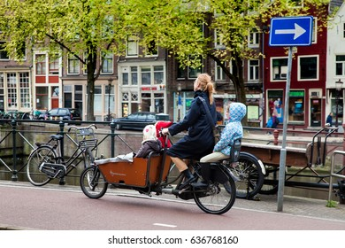 Amsterdam, Netherlands - April, 2017: Mother with three children on the bicycle in Amsterdam, Netherlands