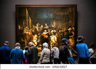 Amsterdam, Netherlands - April, 2017: Visitors watching The Night Watch, Rembrandt's largest and most famous painting in Rijksmuseum's Gallery