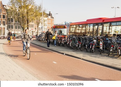 AMSTERDAM, NETHERLANDS - APRIL 22: People go to work by bicycles and buses  on april 22, 2013 in Amsterdam. In Capital of Netherlands are also twice as many bikes then cars.