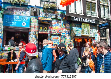 AMSTERDAM, NETHERLANDS APRIL 27: Famous Amsterdam Bulldog coffeeshop in red-light district in the midday, crowd of people on the street on King's Day on April 27,2015.
