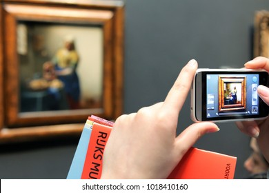 AMSTERDAM, NETHERLANDS - APRIL 3: Visitor and famous painting The Milkmaid from Johannes Vermeer at on April 3, 2014 in Amsterdam