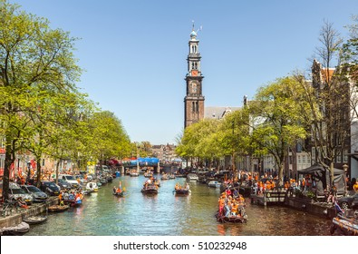 Amsterdam, Netherlands - April 30, 2012: Amsterdam canal with boats and people in orange during the celebration of queensday on April 30, 2012 in Amsterdam.