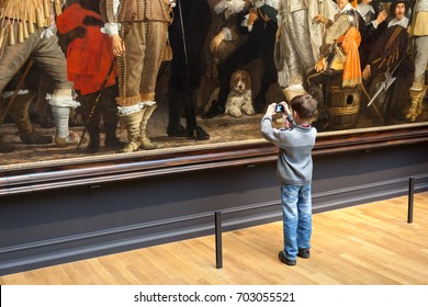 "AMSTERDAM, NETHERLANDS - APRIL 30, 2013: Young admirer of famous painting ""The Night Watch"" from Rembrandt, Rijks museum, Amsterdam, Netherlands"