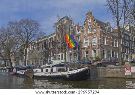 AMSTERDAM, THE NETHERLANDS - APRIL 8, 2013: Gay pride flag over the channel in Amsterdam.
