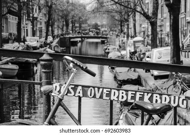 AMSTERDAM, NETHERLANDS – APRIL 8, 2016: Bicycles and boats of the famous amsterdam canals. An old bicycle on the Rosa Overbeekbrug bridge, over the canal the Bloemgracht in the Jordaan area.