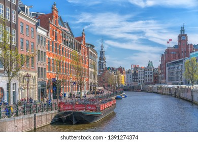 Amsterdam, Netherlands - April 9, 2019: Classic bicycles and historical houses in old Amsterdam. Typical street in Amsterdam with canal and colorful houses in the Dutch style on the Sunset.