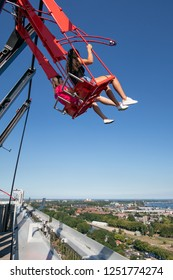 Amsterdam, The Netherlands - August 03, 2018: Two pretty girls at swing at the top of a skyscraper building downtown in Amsterdam