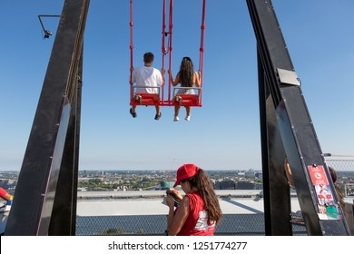 Amsterdam, The Netherlands - August 03, 2018: Young couple at swing at the top of a skyscraper building downtown in Amsterdam