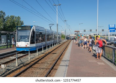 Amsterdam, The Netherlands - August 03, 2018: Passengers waiting at tram station Zeeburg for transportation to Amsterdam Central station