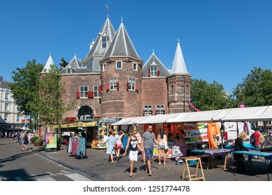 Amsterdam, The Netherlands - August 03, 2018: Nieuwmarkt square with medieval Waag building and people visiting a daily general goods market in the old centre of Amsterdam