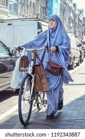 Amsterdam, Netherlands - August 1, 2018: A Muslim with bicycles on the Vethaninstraat street on August 1, 2018 in Amsterdam, Netherlands
