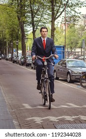 Amsterdam, Netherlands - August 1, 2018: A man in a suit is riding a bicycle on the Vethaninstraat street on August 1, 2018 in Amsterdam, Netherlands