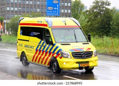 AMSTERDAM, NETHERLANDS - AUGUST 10, 2014: Yellow ambulance car Mercedes-Benz Sprinter at the city street.
