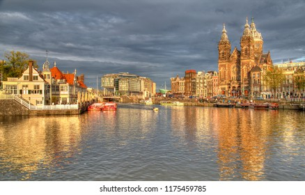 Amsterdam, The Netherlands - August 11, 2017: Saint Nicholas church, tour boats and tourists in historical Amsterdam, The Netherlands on August 11, 2017