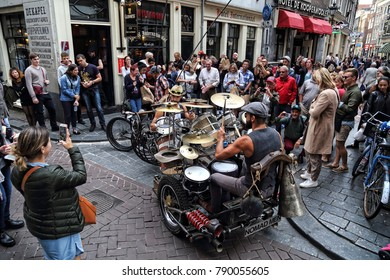 Amsterdam, The Netherlands - August 11, 2017: Tourists stand around two guys playing drums on a threewheeler in a narrow street in historical Amsterdam, The Netherlands on August 11, 2017