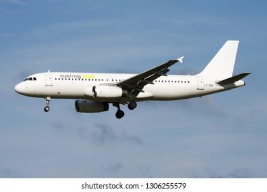 AMSTERDAM / NETHERLANDS - AUGUST 15, 2014: Vueling Airbus A320 LY-VEM passenger plane landing at Amsterdam Schipol Airport