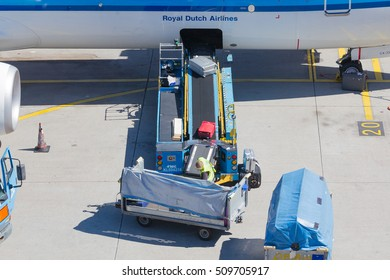 AMSTERDAM, NETHERLANDS - AUGUST 17, 2016: Loading luggage in airplane at Amsterdam Schiphol airport, Netherlands on August 17, 2016. Schiphol is the fourth biggest airport in Europe.