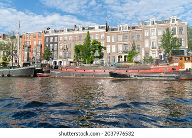 Amsterdam Netherlands - August 17 2017; Boats and buildings alongside Amstel River including one named Waltzing Matilda