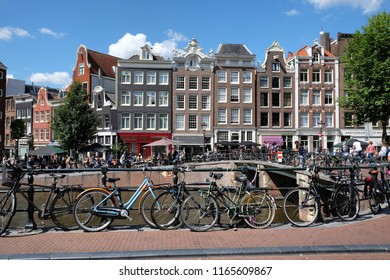 AMSTERDAM, THE NETHERLANDS - AUGUST 18, 2018: Canal scenes. Bicycles line the canals in the Dutch capital