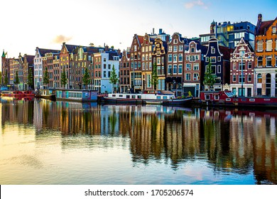 AMSTERDAM, NETHERLANDS - AUGUST 18, 2019 :: Architecture of colorful old buildings with morning light. Famous destination for traveller in Europe.