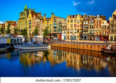 AMSTERDAM, NETHERLANDS - AUGUST 19, 2019 :: Architecture of Damrak street of Amsterdam. Colorful old Buildings. Famous destination for tourist in Europe.