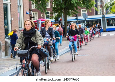 AMSTERDAM, NETHERLANDS - AUGUST 19:  People riding bicycles in historical part in Amsterdam, Netherlands on August 19, 2014