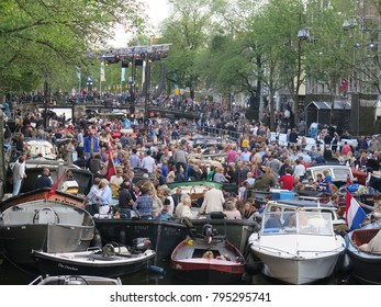 Amsterdam, Netherlands - August 2017: Boats full of people docked altogether in a channel close to the main stage of the classical music Grachtenfestival Canal Festival