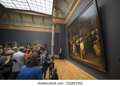 "AMSTERDAM, NETHERLANDS - AUGUST 21, 2014: People with a guided tour watching famous ""the Nachtwacht"" by Rembrandt van Rijn at the national museum Rijksmuseum"
