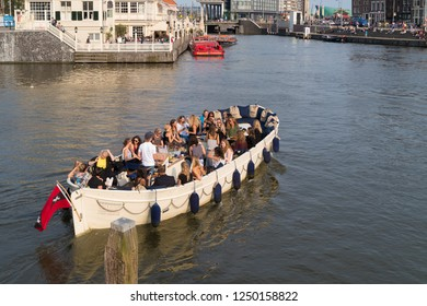 AMSTERDAM, NETHERLANDS - AUGUST 25, 2017:  Boat full with unknown people celebrating a party on an amsterdam canal