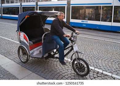 AMSTERDAM, NETHERLANDS - AUGUST 25, 2017:  Unknown man on a bike taxi, a popular way of transportation in the Dutch capital