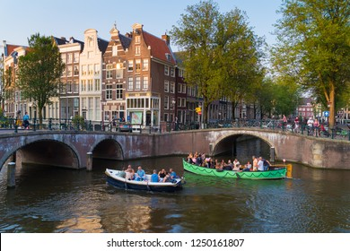AMSTERDAM, NETHERLANDS - AUGUST 25, 2017:  Boats full with tourists enjoying a canal sightseeing tour on the amsterdam canals