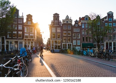 AMSTERDAM, NETHERLANDS - AUGUST 25, 2017:  Sunset over a typical amsterdam canal bridge