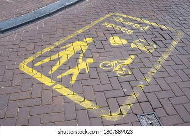 AMSTERDAM, THE NETHERLANDS - AUGUST 30 2020: Yellow signs on the street indicate a Shared Space area in Amsterdam, a concept where priority and rules are lacking for traffic. Focus on the signs