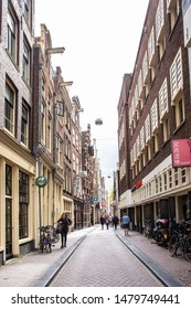 AMSTERDAM, NETHERLANDS- AUGUST 31, 2018:  Street scene from Amsterdam  in the Red Light district during the day with people visible.