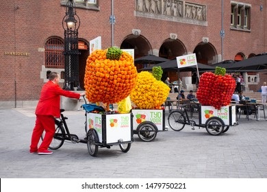 AMSTERDAM, NETHERLANDS - AUGUST 31, 2018:  Street scene in Amsterdam with colorful bell pepper carts and vendors