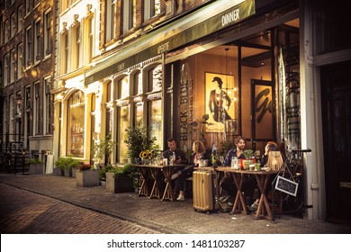 AMSTERDAM, NETHERLANDS - AUGUST 31, 2018:  Street scene from Amsterdam with people dining outdoors at sunset.