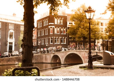 AMSTERDAM, NETHERLANDS - AUGUST 31, 2018:  Street scene with canal, bridge and typical architecture seen in Amsterdam